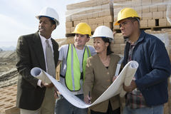 Architects And Workers With Blueprint At Site Royalty Free Stock Photography