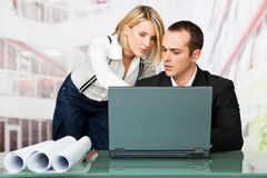 Architects working. Male and female architects discussing behind laptop and blueprints Stock Photo