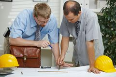 Architects working on blueprint. Architects working at office - planning and looking at blueprint on desk Royalty Free Stock Photo