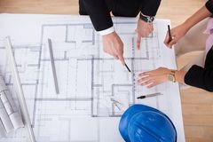 Architects working on blueprint Stock Photography