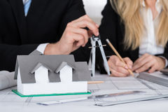 Architects Working On Blueprint With House Model On Desk. Midsection of architects working on blueprint with house model on desk in office Royalty Free Stock Photos