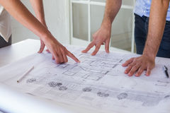 Architects working on blueprints together Stock Image