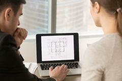 Architects working with building plan on laptop screen, close up Royalty Free Stock Photos