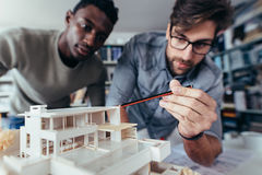 Architects working on new architectural house model. Two young architects working on new architectural house model. Designers looking at house model in studio stock photo