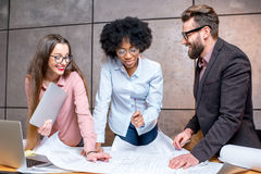 Architects working at the office. Multi ethnic group of architects or designers working together on the architectural plans at the office Royalty Free Stock Images