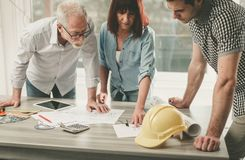 Architects working on plans. At office stock photo
