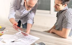 Architects working on plans. At office stock photos