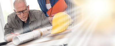 Architects working on plans; multiple exposure royalty free stock image
