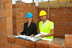 Architects working on site. Two architects with projects working in a house under construction,check out  Workers and tools Stock Photo