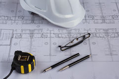 Architects workplace - architectural blueprints with measuring tape, safety helmet, glasses and propelling pencil on table. Top vi Stock Photography