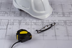Architects workplace - architectural blueprints with measuring tape, safety helmet, glasses and propelling pencil on table. Stock Image