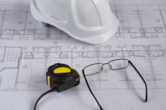 Architects workplace - architectural blueprints with measuring tape, safety helmet and glasses on table. Top view. Royalty Free Stock Photos