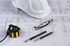 Architects workplace - architectural blueprints with measuring tape, safety helmet and glasses on table. Top view. Royalty Free Stock Image