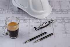 Architects workplace - architectural blueprints with safety helmet, glasses, coffee and propelling pencil on table. Top view. Royalty Free Stock Photos