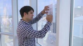 Architects works with sketch, drawing, plan near bright clean office panoramic window. stock video