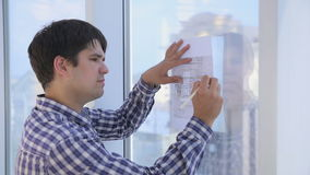Architects works with sketch, drawing, plan near bright clean office panoramic window. stock footage