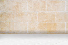 Architectual background made of white mosaic and orange irregular facade. Wall made of old uncared orange stones and floor made of little modern beige ceramic Stock Image