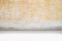 Architectual background made of white mosaic and orange irregular facade. Wall made of old uncared orange stones and floor made of little modern beige ceramic Royalty Free Stock Image