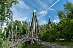 Architectual striking wooden pedestrian bridge. Over a river in a wild natural landscape stock photos