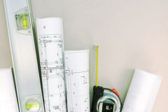 Architectural blueprint rolls with spirit level and tape measure Stock Image