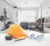 Architectural blueprint with safety helmet and tools over bedroom. With sofa as background stock photos