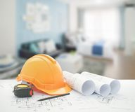 Architectural blueprint with safety helmet and tools over blue color scheme bedroom. With sofa royalty free stock photo