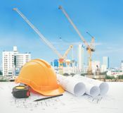 Architectural blueprint with safety helmet and tools over construction site with tower crane. And blue sky stock images