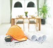 Architectural blueprint with safety helmet and tools over dining table and comfortable chairs. In modern home royalty free stock photo