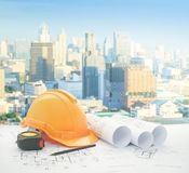 Architectural blueprint with safety helmet and tools over modern business district with high building.  royalty free stock image