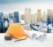 Architectural blueprint with safety helmet and tools over modern high building. Architectural blueprint with safety helmet and tools over modern business stock photography