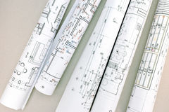 Architectural blueprints and blueprint rolls on desk Royalty Free Stock Photo