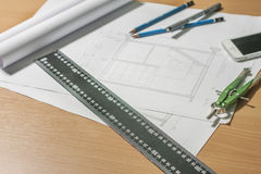 Architectural blueprints and blueprint rolls and a drawing instruments Stock Image