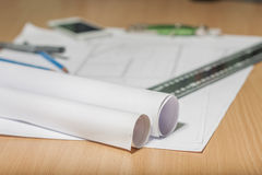 Architectural blueprints and blueprint rolls and a drawing instruments Royalty Free Stock Photography