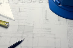 Architectural blueprints and blueprint rolls and a drawing instruments on the worktable Royalty Free Stock Photography