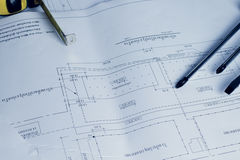 Architectural blueprints and blueprint rolls and a drawing instruments on the worktable Stock Image