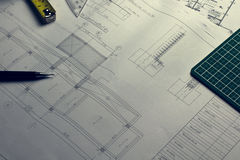 Architectural blueprints and blueprint rolls and a drawing instruments on the worktable Royalty Free Stock Image