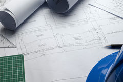 Architectural blueprints and blueprint rolls and a drawing instruments on the worktable Royalty Free Stock Photo