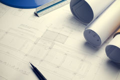 Architectural blueprints and blueprint rolls and a drawing instruments on the worktable Royalty Free Stock Photos