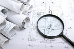 Architectural blueprints, blueprint rolls and magnifying glass on white background. Stock Photo