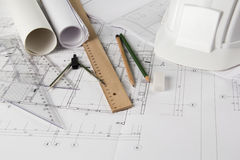 Architectural blueprints and drawing tools. Blueprints, pencils, rulers, drawing compass and a hardhat Stock Image
