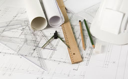 Architectural blueprints and drawing tools. Blueprints, pencils, rulers, drawing compass and a hardhat Stock Photos