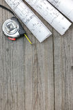 Architectural blueprints with tape measure on gray wooden boards Royalty Free Stock Photo