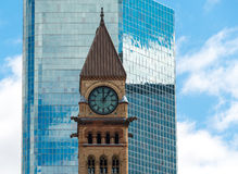 Architectural contrast:Clock tower in Old City Hall in Toronto against modern building. Architectural contrast: Old City Hall with a glass wall of a modern Stock Photos