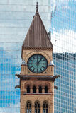 Architectural contrast:Clock tower in Old City Hall in Toronto against modern building. Architectural contrast: Old City Hall with a glass wall of a modern Royalty Free Stock Photo
