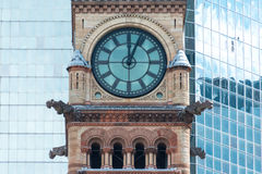 Architectural contrast:Clock tower in Old City Hall in Toronto against modern building. Architectural contrast: Old City Hall with a glass wall of a modern Stock Image