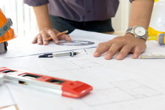 Architectural design and project blueprints drawings-Filtered Image. NInterior designer discussing data and digital tablet and computer laptop with business Royalty Free Stock Image