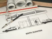 Architectural Design & Tools. An architect designs drawings for new construction using various implements Stock Photo