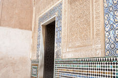 Architectural detail of the Alhambra Palace. Granada, Spain with a tiled door surround with inlaid mosaics and intricate stone carving in relief on the walls Stock Photos