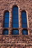 Architectural Detail of Building Wall and Windows. Architectural detail of exterior stone wall and stained glass windows royalty free stock photo