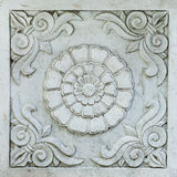 Architectural Detail Carved into Grey Marble: Scrolls and Chrysa. Marble architectural detail showing scrollwork and chrysanthemum flower on public building in Royalty Free Stock Photo